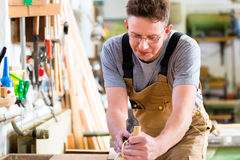 Carpenter with wood planer and workpiece in carpentry Royalty Free Stock Photo