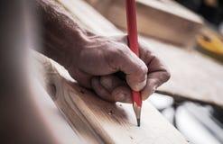 Carpenter Woodwork Job. Contractor Hand with Pencil Closeup Photo royalty free stock photos