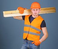 Carpenter, woodworker, labourer, builder on confident face carries wooden beams on shoulder. Hardy labourer concept. Man. In helmet, hard hat and protective royalty free stock image