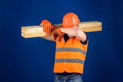 Carpenter, woodworker, labourer, builder on tired face carries wooden beam on shoulder. Tired labourer concept. Man in. Helmet and protective gloves wiping Stock Photography
