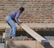 Carpenter At Work. Man placing a large wood brace on a construction project royalty free stock photography