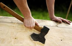 Carpenter at work. Hand holding an axe and chopping the wood. Carpenter at work royalty free stock images