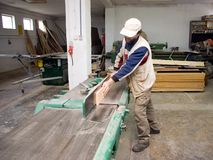Carpenter at work. A carpenter at work, processing some wood, a machine working Stock Photography