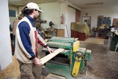 Carpenter at work. A carpenter at work, processing some wood, a machine working Royalty Free Stock Photography