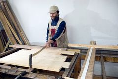 Carpenter at work. A carpenter at work, processing some wood, standing at the table with some wooden planks Stock Images