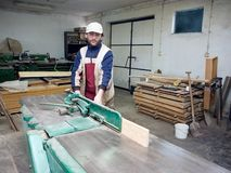 Carpenter at work. A carpenter at work, processing some wood, a machine working Stock Photos