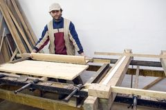 Carpenter at work. A carpenter at work, processing some wood, standing at the table with some wooden planks Royalty Free Stock Photo