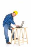 Carpenter at work. With laptop, white background, reflective surface, studio shot Stock Image