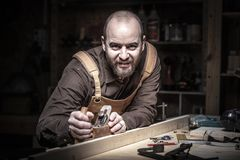 Carpenter at work. Caucasian carpenter at work in his workshop royalty free stock photos