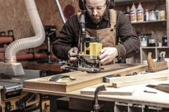 Carpenter at work. Caucasian man using a router in his workshop royalty free stock photography