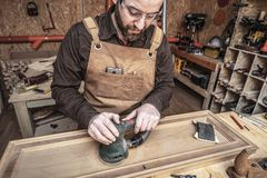 Carpenter at work. Caucasian carpenter at work using a sander royalty free stock photography
