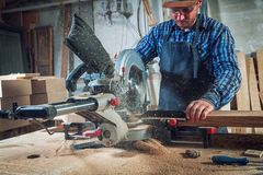 Carpenter work with circular saw stock images
