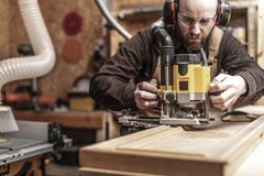 Carpenter at work. Craftman portrait using a vertical router stock photos