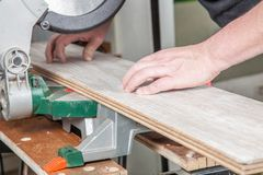 Carpenter daily work. A Carpenter is cutting the laminate with a buzz saw stock photos