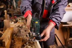 Carpenter at work with electric planer joinery. The carpenter hands when working with electric planer joinery Royalty Free Stock Image