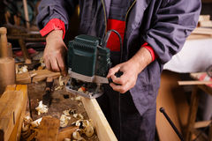 Carpenter at work with electric planer joinery. The carpenter hands when working with electric planer joinery Stock Photo