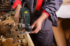 Carpenter at work with electric planer joinery. The carpenter hands when working with electric planer joinery Royalty Free Stock Images