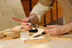 Carpenter at work gluing piece of wood Royalty Free Stock Photography