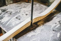 Carpenter at work in his atelier works wood by creating objects. Close view of a circular saw while cutting Royalty Free Stock Image