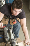 Carpenter at work on job using power tool Stock Photo