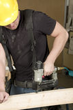 Carpenter at work on job using power tool Royalty Free Stock Photo