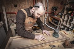 Carpenter at work. Man sanding wood in his workshop stock photo