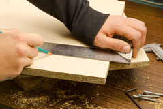 Carpenter work. Carpenter marks furniture parts in the workplace stock photo