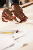 Carpenter at work. Carpenter measuring and tracing lines with a ruler on a wooden surface Royalty Free Stock Image