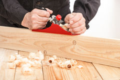 Carpenter at work. Middle aged carpenter planing the surface of a plank of wood Stock Image