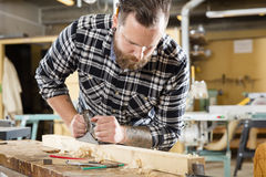 Carpenter work with plane on wood plank in workshop Royalty Free Stock Images