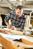 Carpenter work with plane on wood plank in workshop Stock Photos