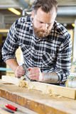 Carpenter work with planer on wood plank in workshop Stock Images