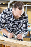 Carpenter work with planer on wood plank in workshop Stock Photography