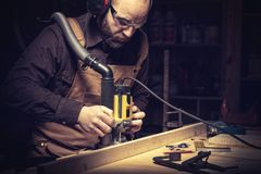 Carpenter at work. Portrait of carpenter using a vertical router stock photos