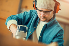 Carpenter at work. Safety-conscious contractor or homeowner working with nail gun Royalty Free Stock Photos