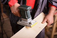 Carpenter at work with the sander Stock Photography