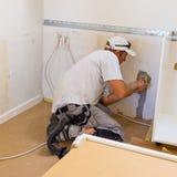 Carpenter at work with screwdriwer. Carpenter mounting new IKEA kitchen Royalty Free Stock Photos