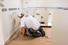 Carpenter at work with screwdriwer. Carpenter mounting new IKEA kitchen Royalty Free Stock Image
