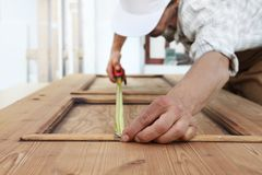 Free Carpenter Work The Wood, Measuring With Meter Tape A Wooden Vintage Door Royalty Free Stock Image - 125141096