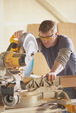 Carpenter. At work using chop saw power tool royalty free stock images