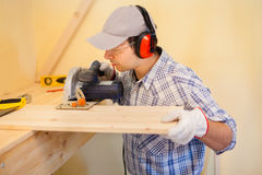 Carpenter at work using a circular saw Stock Photography