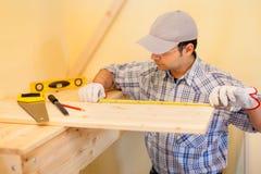 Carpenter at work using a measuring tape Stock Image