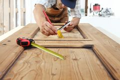 Carpenter work the wood, measuring a wooden vintage door. Carpenter work the wood, measuring with tape meter on wooden vintage door stock photos