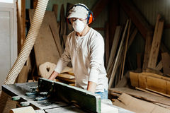 Carpenter at work. Carpenter working with Industrial tool in wood factory wearing safety glasses and hearing protection Stock Photos