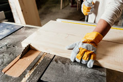 Carpenter at work. Carpenter working with Industrial tool in wood factory wearing safety gloves stock images