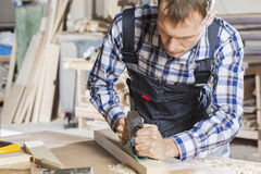 Carpenter at work. Carpenter working with plane in his studio Royalty Free Stock Image