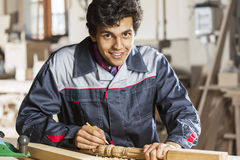 Carpenter at work. Young carpenter working with cutter in his studio Royalty Free Stock Image