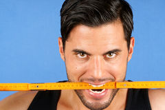 Carpenter worker biting a wooden metric ruler Royalty Free Stock Photos
