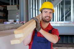 Carpenter worker holding wooden boards. Carpenter worker with helmet holding wooden boards Royalty Free Stock Photography