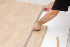 Carpenter worker installing laminate board during flooring work Stock Photo